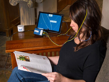woman reading while doing neurofeedback at home
