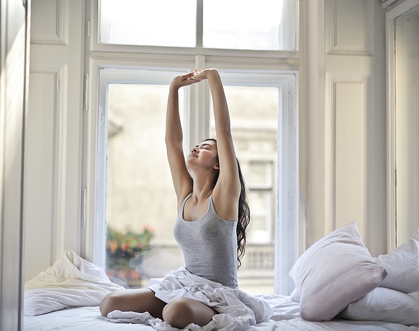 woman-sitting-on-white-bed-while-stretching-900px