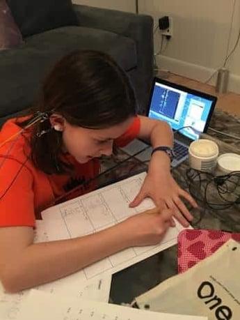 teen with neurofeedback machine while doing homework