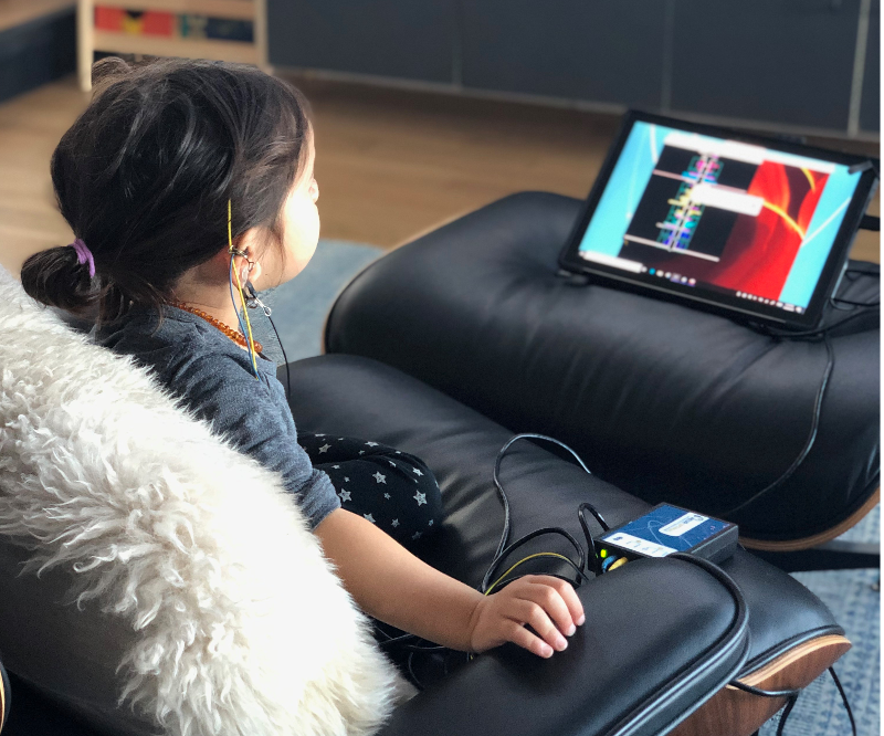 child sitting in front of a neurofeedback machine